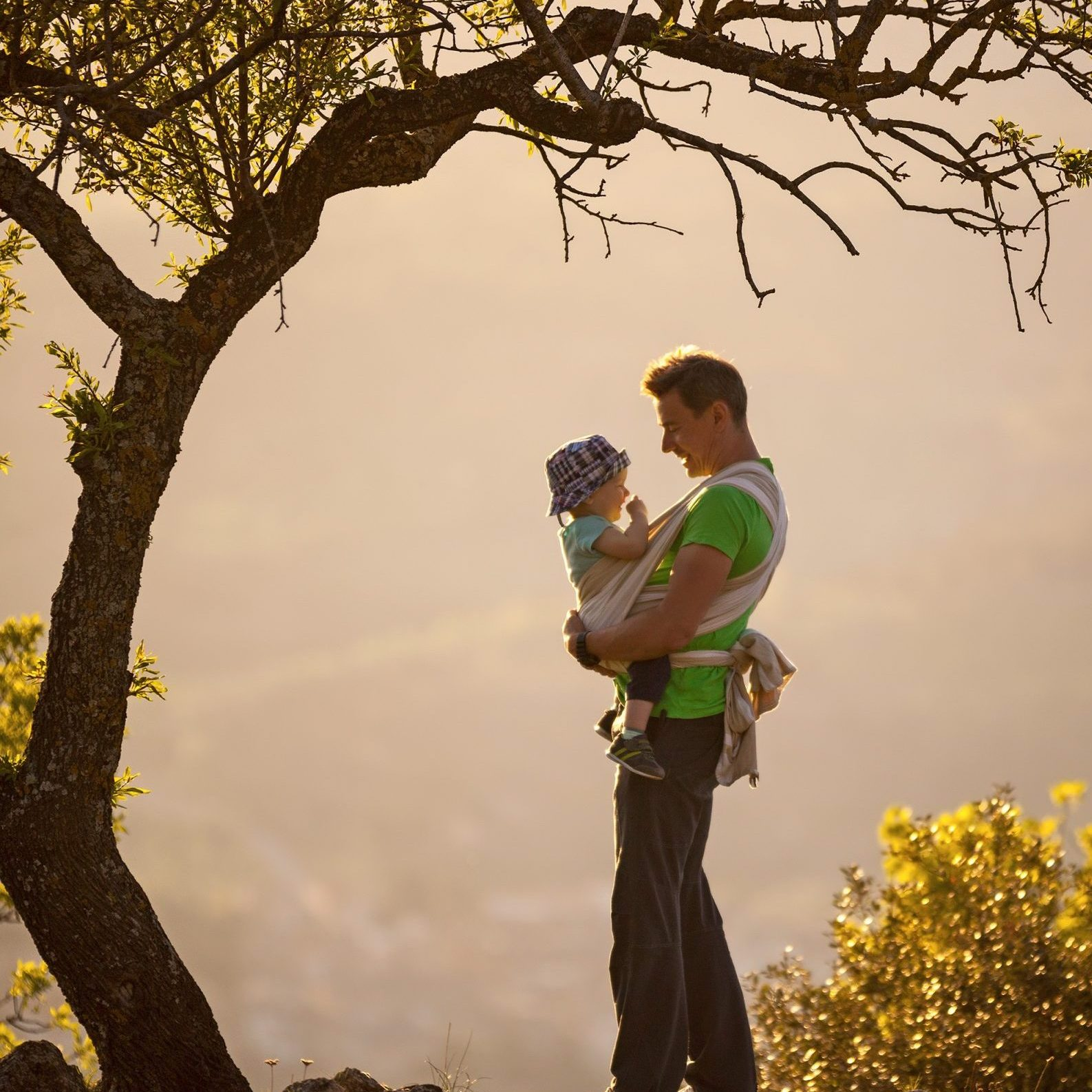 Father carrying his son in sling outdoors